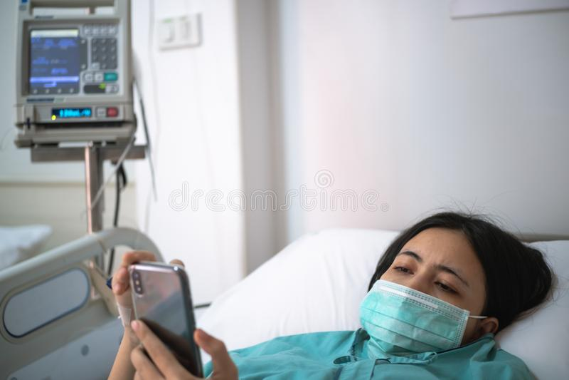 Configuração do paciente da jovem mulher na cama no hospital e no smartphone do uso imagem de stock