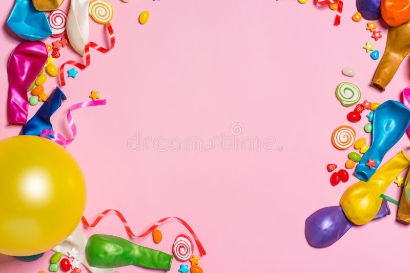 Configuração do plano da celebração Doces com artigos coloridos do partido em vagabundos cor-de-rosa foto de stock royalty free