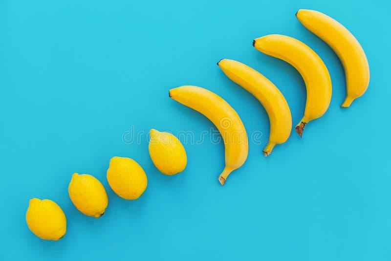 Configuração do plano do verão bananas amarelas com os limões na linha no pape azul foto de stock