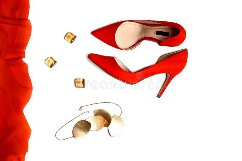 Configuração lisa à composição do equipamento do partido: sapatas vermelhas, acessórios, joia no fundo branco, isolado imagem de stock