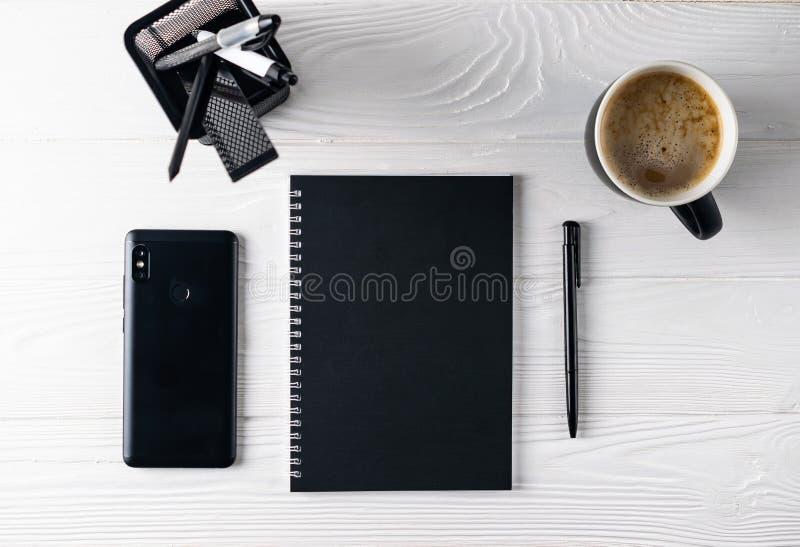 Configuração lisa aérea dos artigos de papelaria do preto do negócio do escritório fotografia de stock
