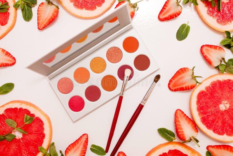 Configuração lisa bonito com a paleta dos cosméticos com fruto fresco, morangos e toranja cortada ou laranja vermelha, folhas de  fotografia de stock royalty free
