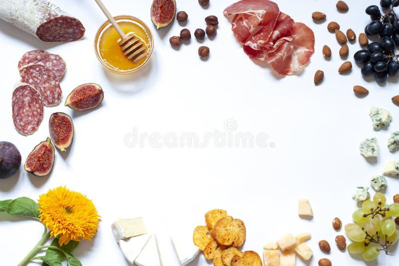 A configuração lisa branca com porcas, mel do alimento dos Antipasti, curou a carne, o salame, os queijos, as uvas e os figos imagem de stock royalty free
