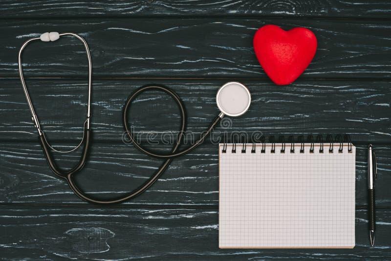 configuração lisa com coração vermelho arranjado, estetoscópio e o caderno vazio no tabletop de madeira escuro, saúde do mundo imagens de stock