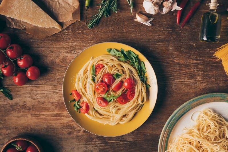 configuração lisa com massa italiana tradicional com tomates e rúcula na placa na tabela de madeira fotografia de stock royalty free