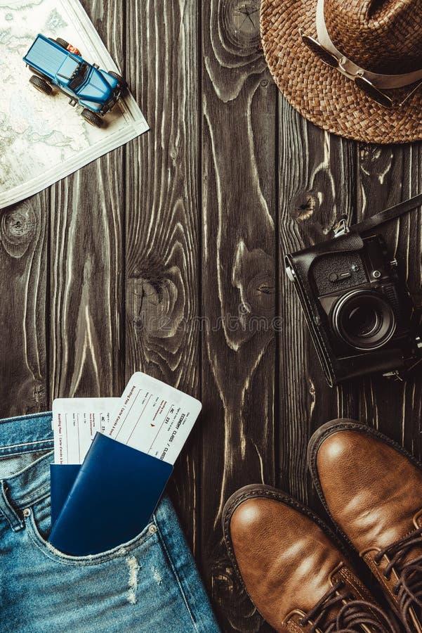 a configuração lisa com sarja de Nimes arfa, sapatas, chapéu de palha, câmera retro da foto, passaportes com os bilhetes na obscu imagem de stock royalty free