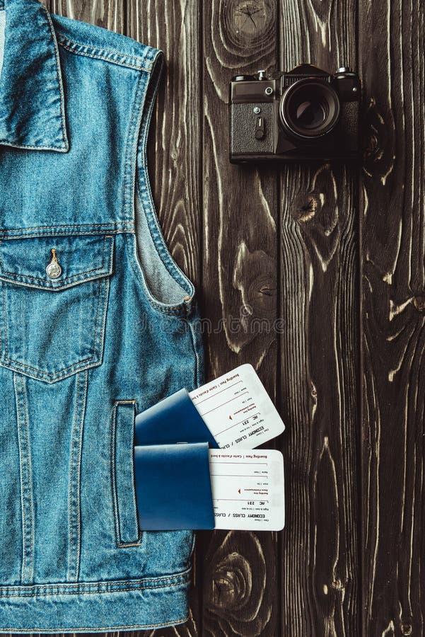 configuração lisa com veste da sarja de Nimes, passaportes, bilhetes e a câmera retro da foto na obscuridade fotografia de stock