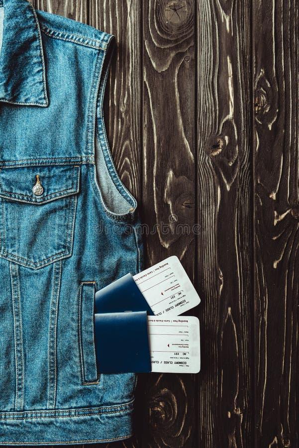 configuração lisa com veste, passaportes e bilhetes da sarja de Nimes na obscuridade imagem de stock royalty free