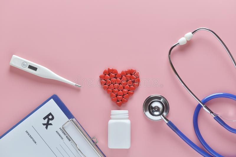 Configuração lisa da forma vermelha do coração de comprimidos da medicina e para medicar o equipamento no fundo cor-de-rosa foto de stock
