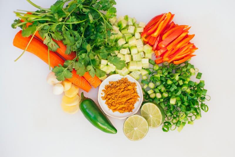 Configura??o lisa de legumes frescos cortados Cenoura saud?vel, cebola verde, salsa, cal, alho, jalapeno contra o fundo branco ve fotografia de stock