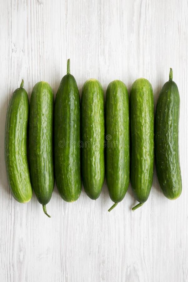 Configuração lisa de pepinos verdes orgânicos crus no fundo de madeira branco Vista superior, de cima de, aérea imagens de stock