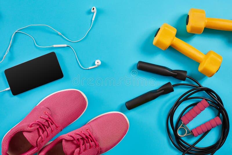 A configuração lisa disparou das sapatilhas, da corda de salto, dos pesos e do smartphone no fundo azul imagem de stock royalty free