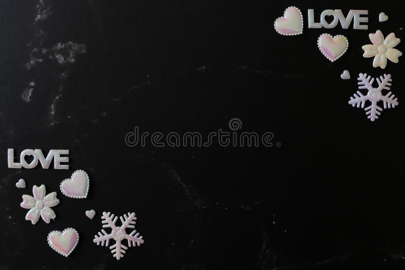 A configuração lisa do fundo de mármore preto decora com brilho da pérola branca cor-de-rosa dos corações, da letra do AMOR, dos  imagem de stock