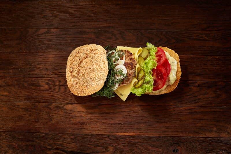 Configuração lisa do hamburguer americano tradicional com alface, queijo, cebola e tomate no fundo de madeira imagem de stock