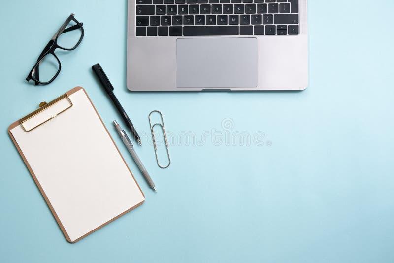 Configuração lisa do negócio: mesa com caderno, lápis, vidros na tabela azul imagens de stock