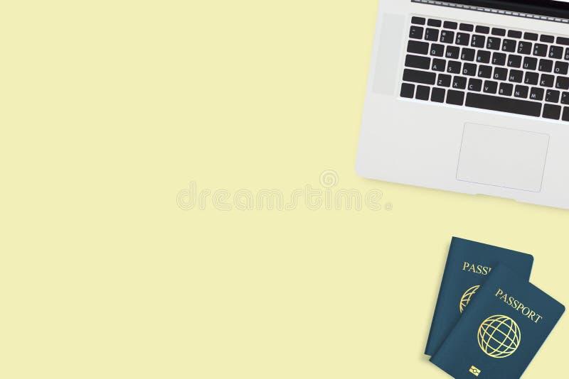 Configuração lisa do portátil do computador de dois passaportes no amarelo pastel fotografia de stock