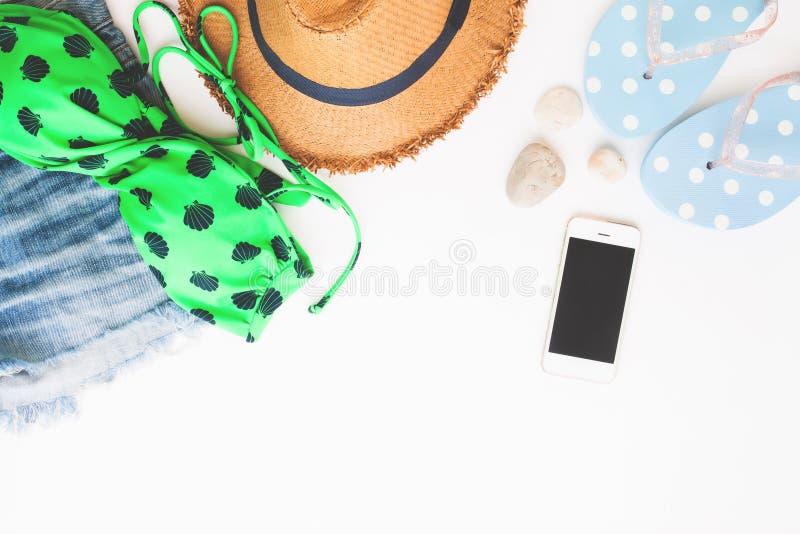 Configuração lisa dos artigos da praia e do telefone esperto, conceito do verão no fundo branco imagem de stock