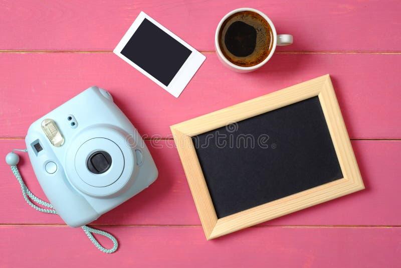 Configuração lisa, mesa da tabela da mulher da vista superior Espaço de trabalho feminino da mesa com câmera instantânea, quadro  foto de stock