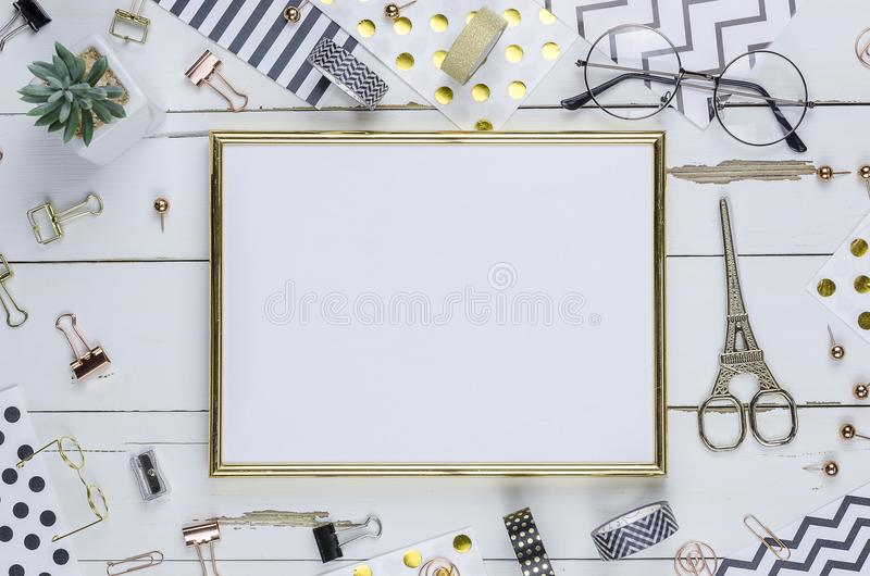 Configuração lisa, mesa de madeira branca e quadro dourado Grampeador do ouro, teste padrão do ouro da listra, lápis parte superi foto de stock royalty free