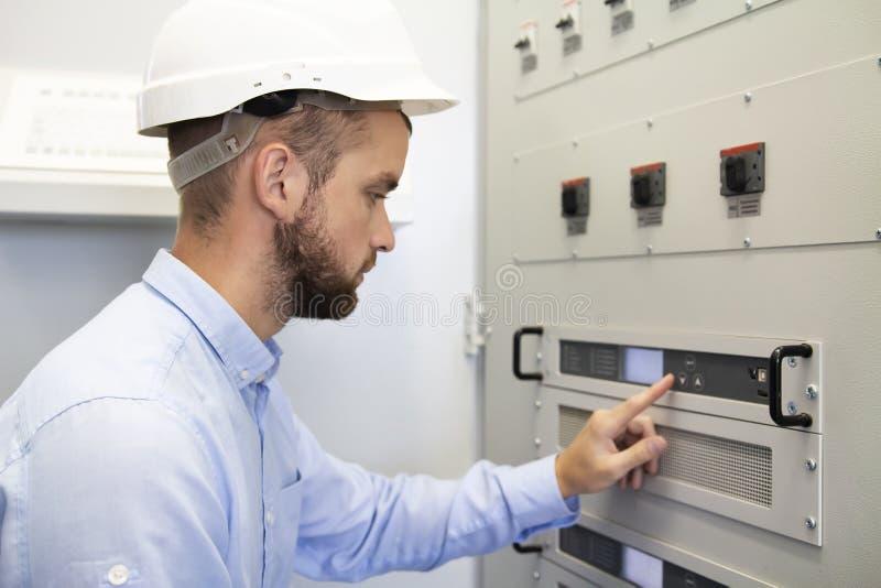 Configurates do homem do serviço do eletricista do controlador elétrico Trabalhos de manutenção Serviços de engenharia no complex foto de stock royalty free