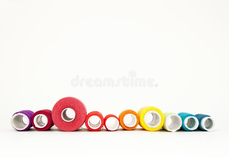 Configuration d'appartement avec les bobines color?es de fil de coton, fil de broderie, bobines d'arc-en-ciel, moquerie, vue sup? photographie stock