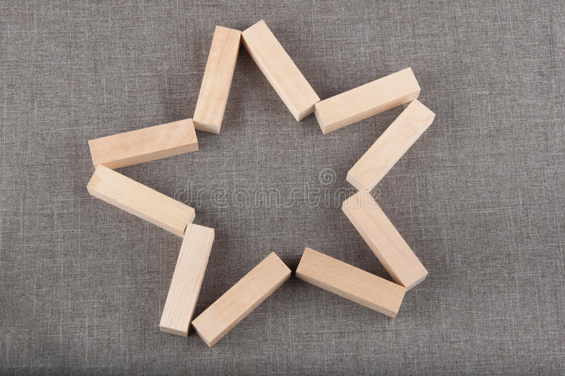 Configuration en bois de briques dans la forme de l'étoile sur le fond gris photographie stock