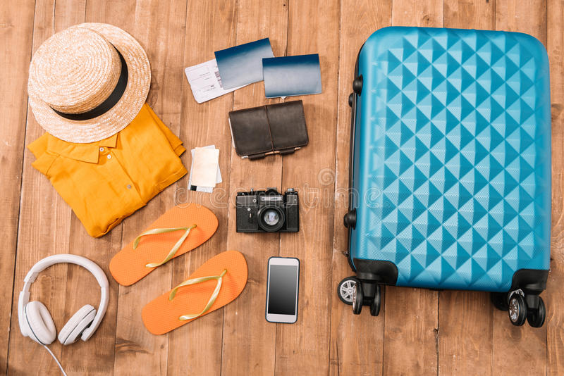 Configuration plate avec des accessoires de voyage sur le plancher en bois images stock