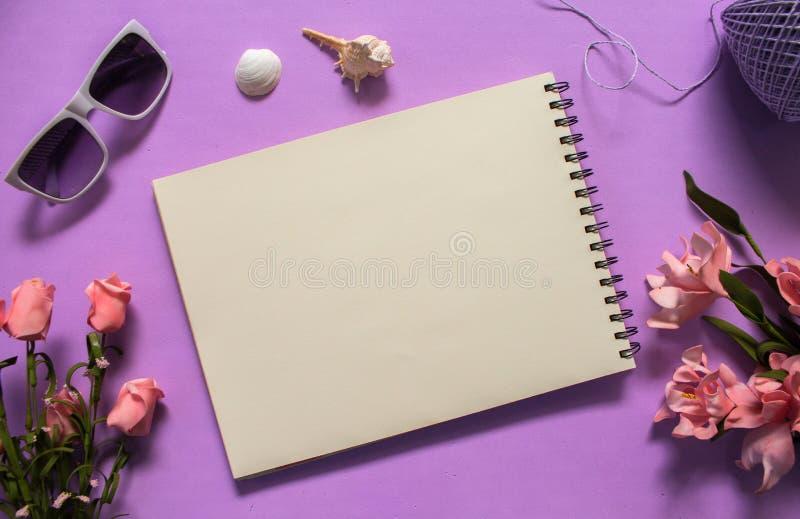 Configuration plate avec le livre blanc et les lunettes de soleil sur le fond violet Bouquet romantique de fleur de rose de rose image stock