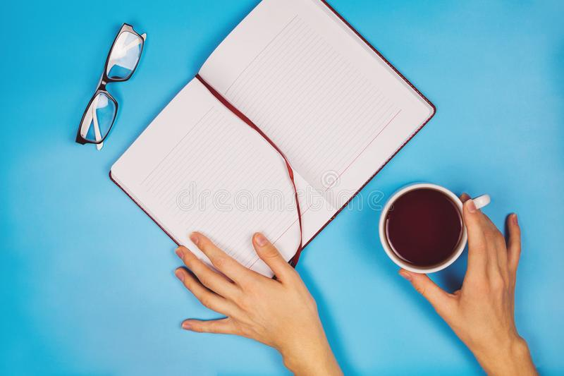 Configuration plate avec le ` s de main de femme tenant une tasse de thé noir, de planificateur et de verres images libres de droits