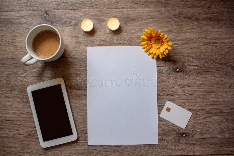 Configuration plate avec une tasse de café, de livre blanc, de carnet, de comprimé et de creditcard blanc photo stock