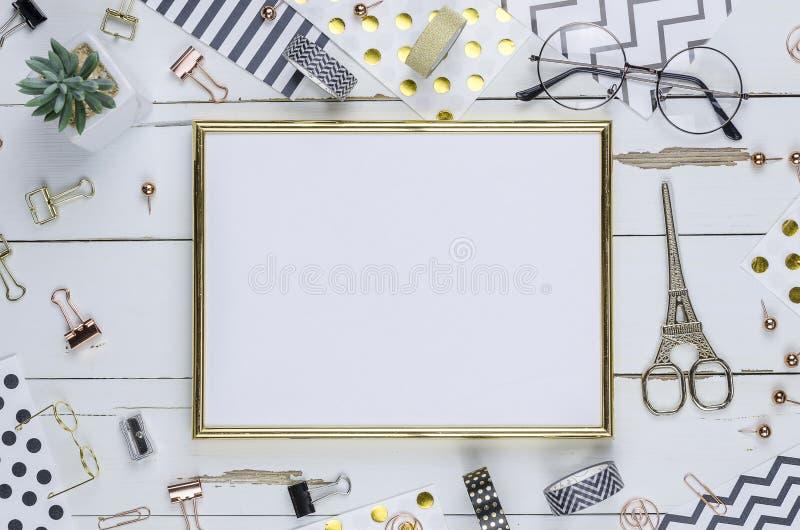 Configuration plate, bureau en bois blanc et cadre d'or Agrafeuse d'or, modèle d'or de rayure, crayon dessus de vue Tableau  Maqu photo libre de droits
