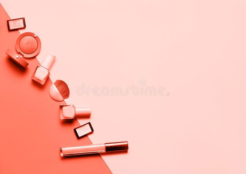 Configuration plate créative des vernis à ongles lumineux de mode et du cosmétique décoratif sur colorés en couleurs de corail vi photos stock