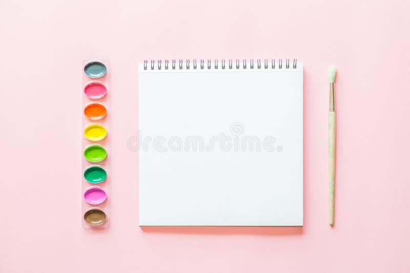 Configuration plate cr?ative des palettes d'aquarelle, brushe de peinture, livre blanc Lieu de travail d'artiste sur un fond en p illustration stock