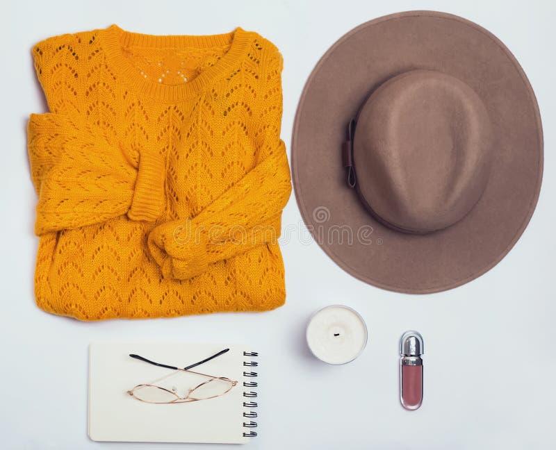 Configuration plate d'automne avec les vêtements féminins sur le fond blanc image stock