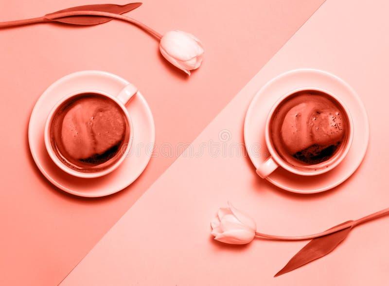 Configuration plate de l'image minimalistic de deux tasses de café et de tulipes colorés dans le corail vivant photographie stock