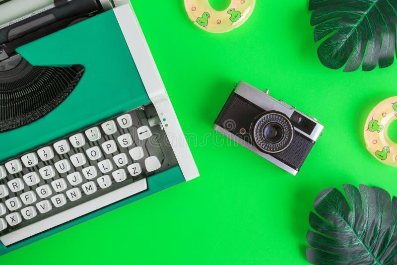 Configuration plate de machine à écrire avec la rétro caméra et les flotteurs gonflables avec des feuilles de monstera abstraites photos libres de droits