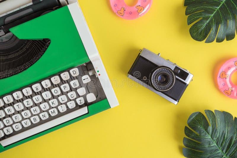 Configuration plate de machine à écrire avec la rétro caméra et les flotteurs gonflables avec des feuilles de monstera abstraites photographie stock