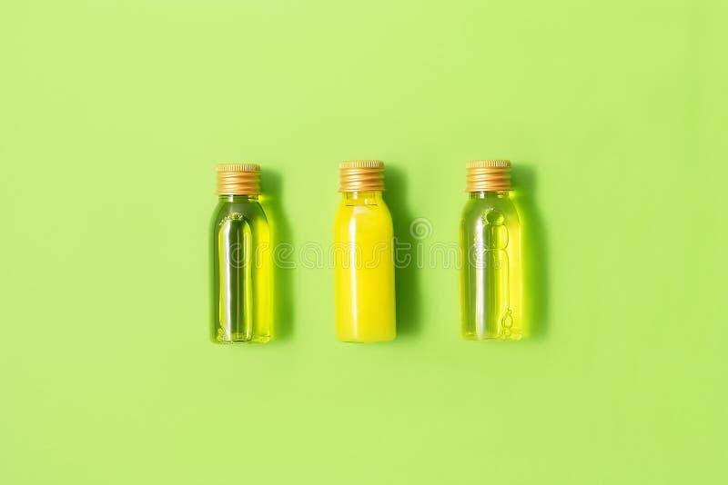 Configuration plate de trois petites bouteilles de maquette avec les produits cosmétiques de station thermale sur le fond vert Fe images stock