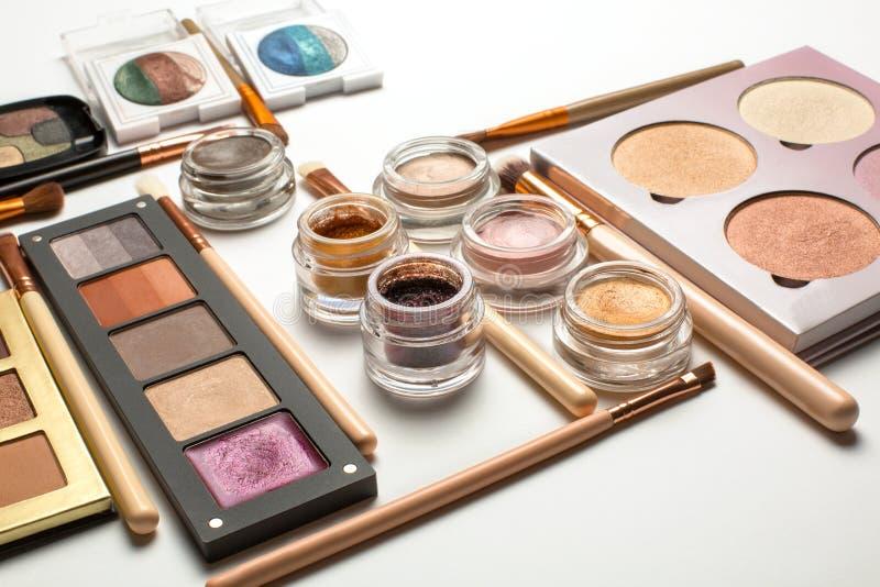 Configuration plate des palettes de fard à paupières, des barres de mise en valeur et des brosses de maquillage images libres de droits