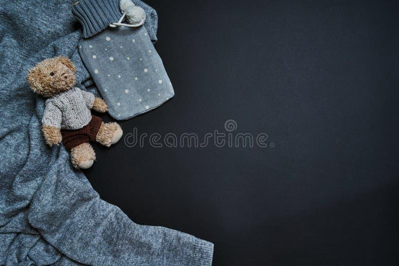 Configuration plate du réchauffeur et du jouet hotty en caoutchouc d'ours sur le chandail Concept d'horaire d'hiver photo libre de droits