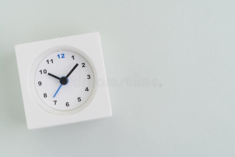 Configuration plate du réveil rectangulaire blanc sur le fond blanc de texture avec l'espace de copie employant comme temps, date photos stock
