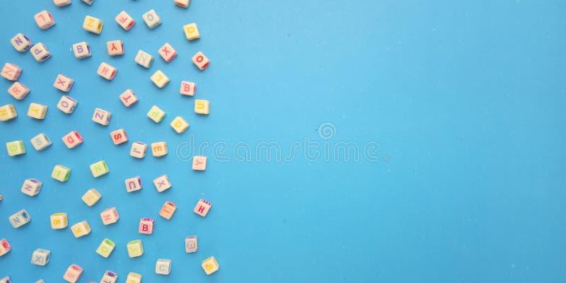 Configuration plate, fond bleu et conception en plastique d'?l?ment de perle de cube en alphabet pour le message, citation, place image stock