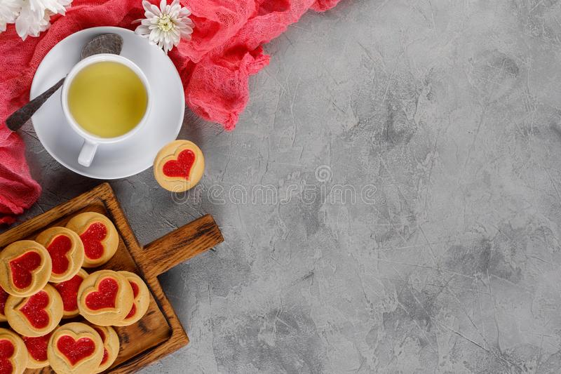 Configuration plate La tasse avec le thé et les biscuits avec un coeur sur un conseil décoratif est un ornement des fleurs fraîch image stock