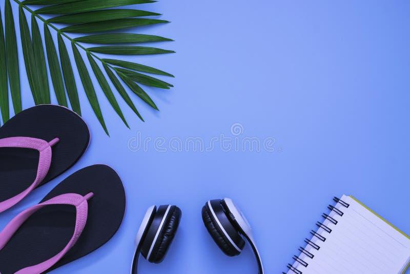 Configuration plate, vue supérieure avec la paume tropicale de pantoufles, d'écouteur, de carnet et de feuille verte pour le conc photographie stock libre de droits