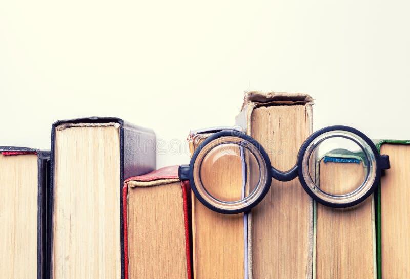 Configuration ronde noire en verre sur une pile de vieux livres battus photographie stock libre de droits