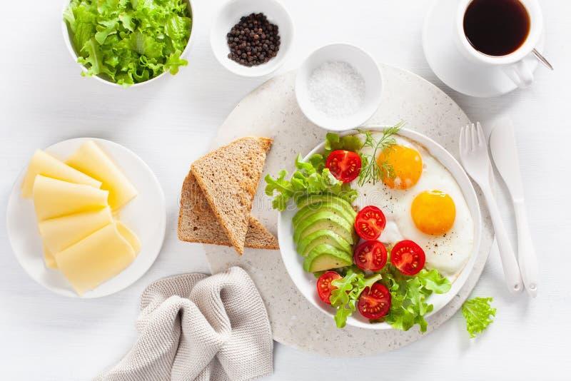 Configuration saine d'appartement de petit déjeuner oeufs au plat, avocat, tomate, pains grillés photographie stock libre de droits