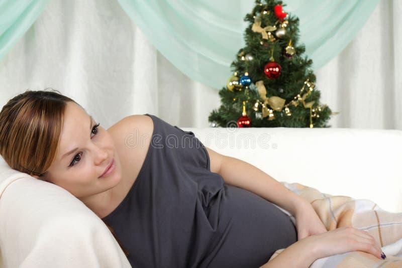 Configurations de femme enceinte de jeunes sur un sofa photographie stock