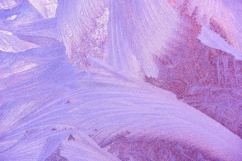 Configurations de gel sur la glace d'hublot en hiver Texture en verre givré bleu et pourpre photo stock