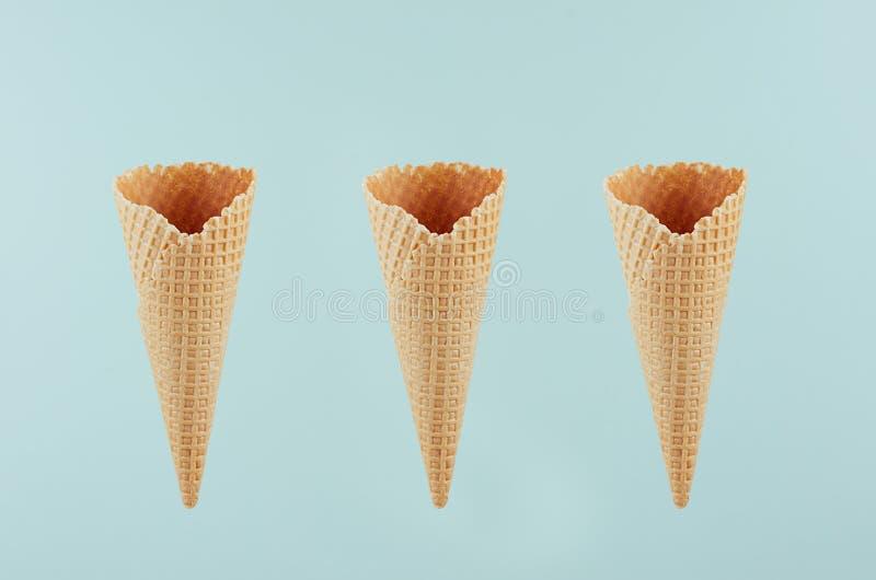 Configure de três cones de gelado torrados vazios no fundo verde, trocista para a propaganda, projeto, menu, alimento do verão imagem de stock royalty free