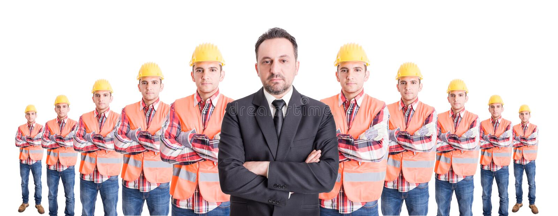 Confindent affärsman och ett lag av byggnadsarbetare royaltyfria foton